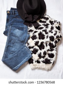 Set of casual female clothes: black and white sweater with leopard pattern, blue skinny jeans and black hat. Back view.