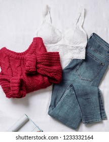 Set of casual female clothes: underwear white lace top ,knitted large viscous red sweater, blue skinny jeans on white background. Top view.