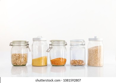 Set of cereals in a glass jar on a white background, rice chickpeas lentil oats millet healthy food and diet concept