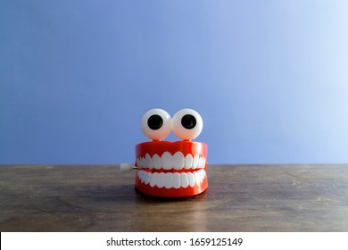 A set of chattering toy teeth with eyes, looking like a cartoon character or mascot. The concept is to encourage children to brush their teeth. Image has a plain, blank background for adding text.