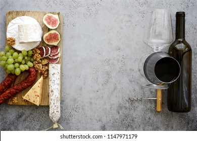Set of cheeses and salami on gray table. Snacks for wine