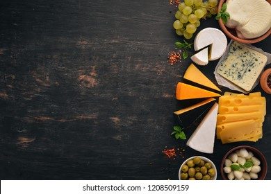Set cheeses. Suluguni, blue cheese, mozzarella, maasdam, brie cheese. Top view. On a black wooden background. Free copy space.
