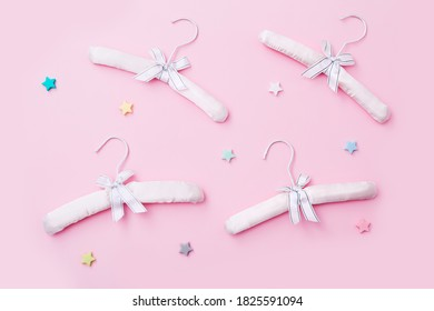 Set of children's clothes hangers on a pink background. Top view