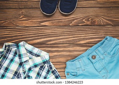 Set of children's clothing for the boy. Blue pants, shirt and sneakers on wooden background. Horizontal color photo.