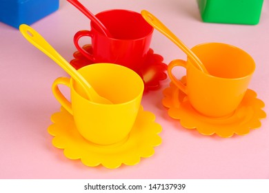 Set of children's dishes on light pink background