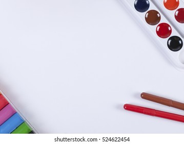 A set of children's watercolors to a set of plasticine on a white background