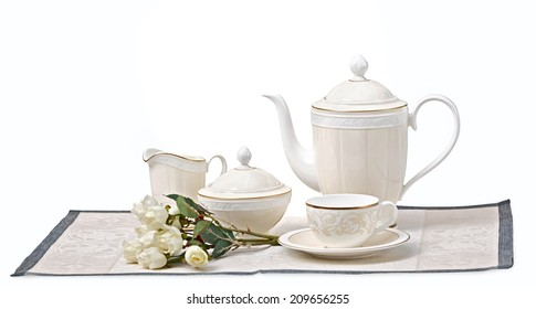 set of china consists of dish, kettle and cups on a white background