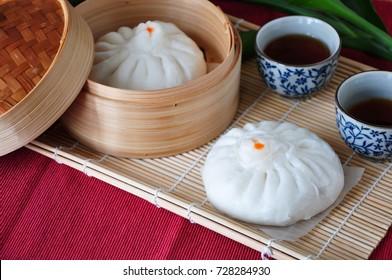 Set of Chinese pork bun with hot tea on bamboo mat