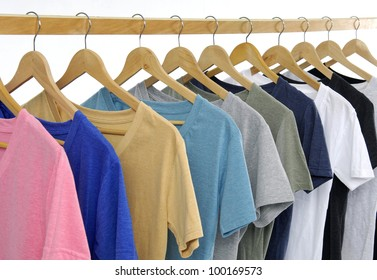 Set of Choice of man clothes of different colors on wooden hangers