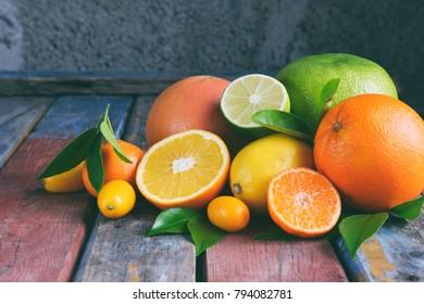Set of citrus on wooden background: orange, mandarin, lemon, grapefruit, lime, kumquat, tangerine. Fresh organic juicy fruits. Source of vitamin C. Healthy food concept. Copy space