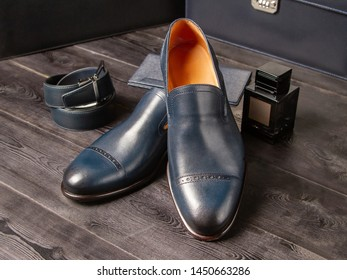 Set of classic men's blue shoes, wallet, trouser belt and a bottle of men's perfume on the boardwalk background. Close-up. Men's shoes of Italian designers. Style of wealthy people