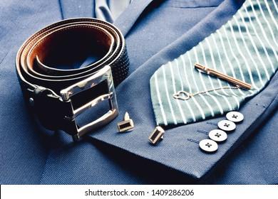Set of classic mens clothes - blue suit, black belt and striped blue. Fashion background. Men's accessories set. Top view. Copy space for text.
