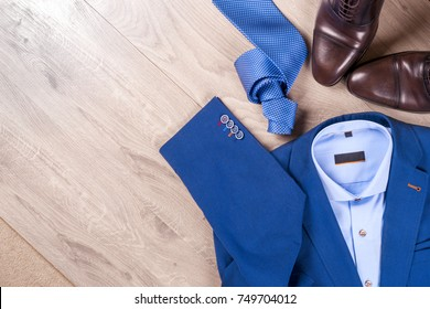 set of classic mens clothes - blue suit, shirts, brown shoes, belt and tie on wooden background. Fashion. Men's accessories set. Top view. Copy space for text.