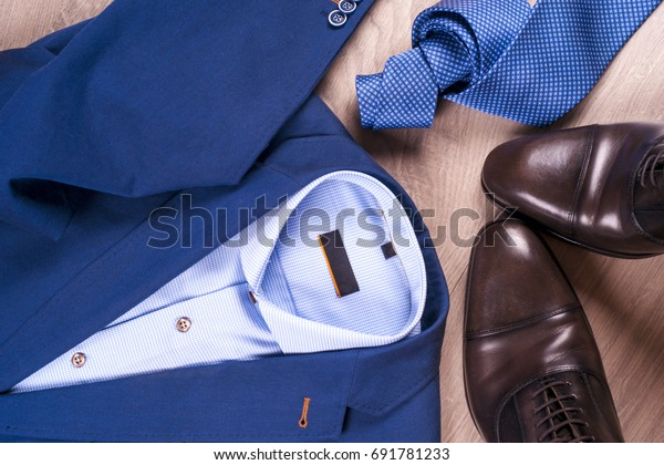 set of classic mens clothes - blue suit, shirts, brown shoes, belt and tie on wooden background. Men's accessories set. Top view. Copy space for text.
