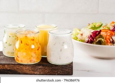 Set of classic salad dressings - honey mustard, ranch, vinaigrette, lemon & olive oil,  on white marble table, copy space