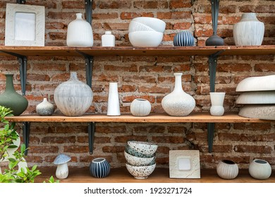 Set of clay pot and ceramic kitchenware which is kept on the wooden shelf in red brick wall storage room. Interior object photo.