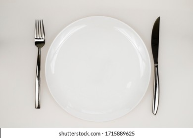set of clean dishes, plate, fork, knife
