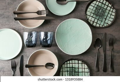 Set of clean tableware on grey background
