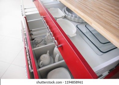 Set of clean tableware in open kitchen drawers