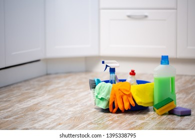 Set of cleaning supplies on floor in kitchen. Space for text