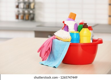 Set of cleaning supplies on table in kitchen. Space for text