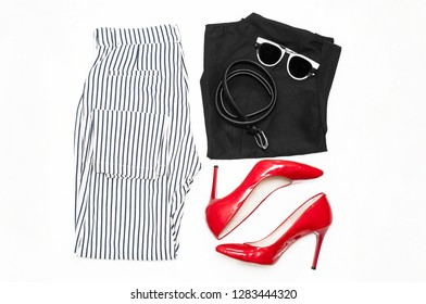 A set of clothes and accessories. Fashionable lady. Striped trousers, red patent leather shoes, a black blouse, a belt, and sunglasses on a white background. Flat lay. Top view