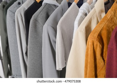 Set of clothes of different men's coat on wooden hangers