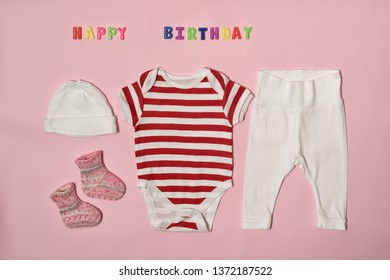 e98488cbfdcf3 Set of clothes for the newborn. Colored inscription happy birthday on a pink  background.
