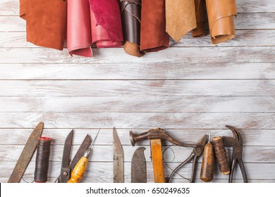 Set of cobbler tools and a lot of brightly colored leather in rolls on the wooden background. Space for text.