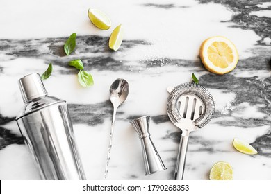 A set of cocktail tools, lime, lemon, sugar, ice, ingredients for ,top view, marble background