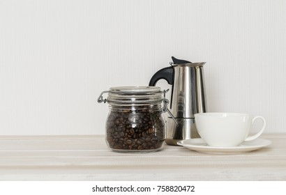 Set for coffee making: cup of coffee, coffee beans, percolator on white wooden table