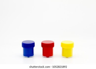 Set of color gouache jars and primary color acrylic paints on white background.