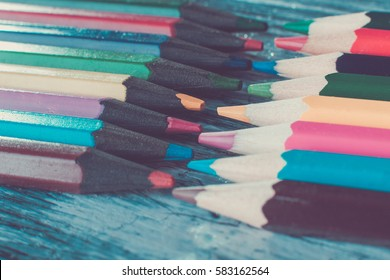 Set of color pencils on wooden background. Macro. Close up. Toned photo.