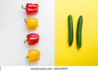 Set of colored bell peppers on white background and cucumber on yellow background. Top view