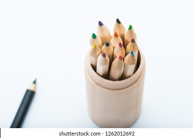 set of colored pencils packed in a wooden cup