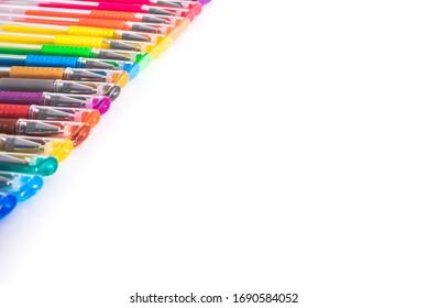 Un juego de plumas de colores dispuestas en una mesa estudio blanca con espacio aislado.