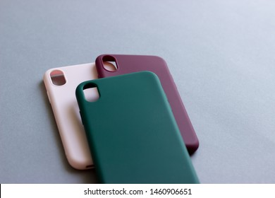 Set of colored silicone cases for the smartphone on the grey background.
