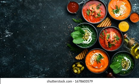 Set of colored soups. Spinach soup, tomato cream soup and carrot puree soup. Healthy food. On a black stone background.