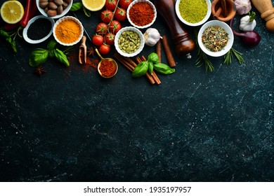 Set of colored spices in bowls and herbs on a black stone background. View from above. Top view.