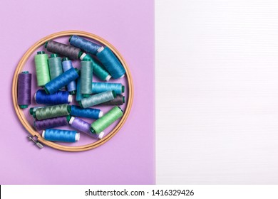 Set of colored thread coils on plastic pink background, sewing and tailoring. Banner, book or magazine cover.