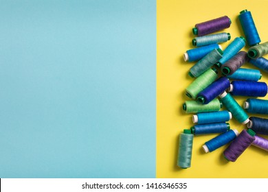 Set of colored thread coils on yellow background, sewing and tailoring. Textile blue background. Space for text in the left. Banner, book or magazine cover,Top view, flat lay