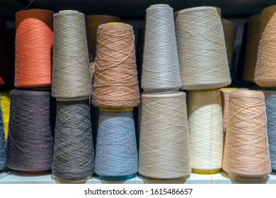 Set of colored threads for sewing on coils. Pile of big colorful spools of thread. Colored thread spools of thread large class, textiles, background.