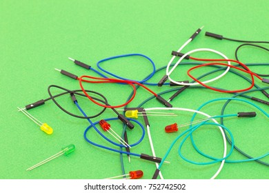 Set of colorful cables and diode on green background