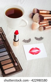 Set of colorful cosmetics and a coffee cup on white wooden background