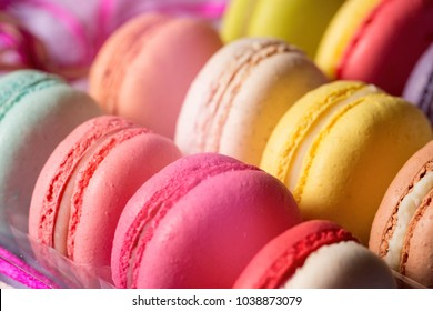 Set of colorful different french cookies macaroons in a plastic box for tasty background.