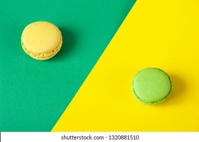 Set of colorful French macaroni cakes on yellow and green neon colored paper background