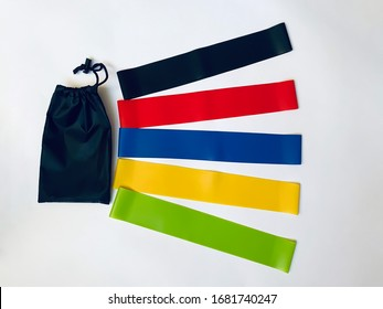 a set of colorful latex rubber bands for fitness and a black cover for them on a white background.  sports concept.  top view, flat lay, copy space - Shutterstock ID 1681740247