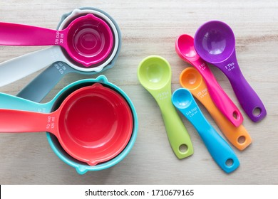 Set of colorful measuring cups and measuring spoons use in cooking lay on wood tabletop in top view.