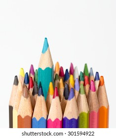 A set of colorful pencils on a white background. One pencil is getting a headstart.