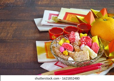 Set of colorful snack, Mandarin orange, Tea, candle, incense stick and joss money paper for worship to Taoism Gods / Goddess and ancestors in Chinese cultures in all Chinese Festival. Copy space